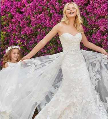 Woman in Justin Alexander wedding gown being followed by flower girls
